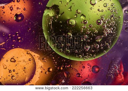 Unusual colorful background with oil drop circles and air bubbles that reflect yellow, orange, purple, green and red colors. Color spots intentionally unfocused. Cosmic space and galaxy concept.