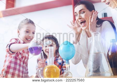 You driving out of my mind. Shocked female teacher of chemistry screaming while watching the group of elementary students disobeying her and trying to mix different chemical substances