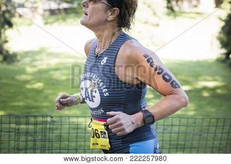 NEW YORK - JULY 16 2017: CAF athlete runs through Riverside Park during the NYC Triathlon Race in Central Park. The run is 10k and the race is the only International Distance triathlon in NYC.