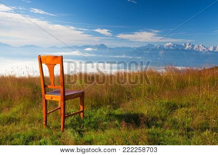 Old wooden chair on the top in Carnic Apls in Austria.Inverse weather and view of the mountains in Slovenia.