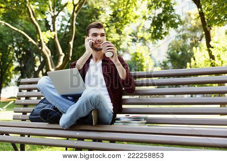 Pensive young man talking on mobile, working on laptop and having coffee, sitting in park on bench. Technology, communication, education and remote working concept, copy space