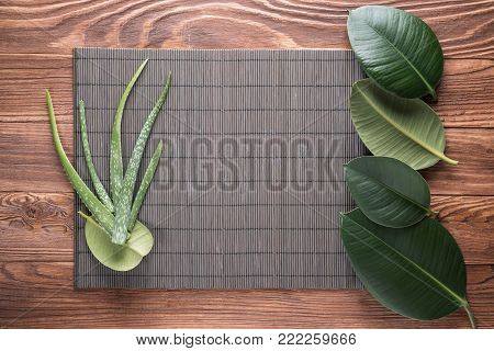 Aloe vera leaves on wooden table. Natural cosmetic ingredients with copy space. Fresh aloe vera plant on wooden board, flat lay. Spa concept, top view.