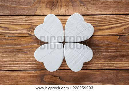 Abstract clover on wood background, top view, flat lay.  Abstract white wooden clover, close-up.