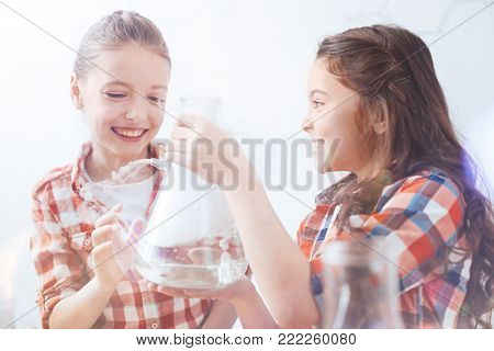 So much fun. Two young ladies getting pretty excited while holding a fuming vacuum flask and chatting about the chemical experiment held by their teacher.