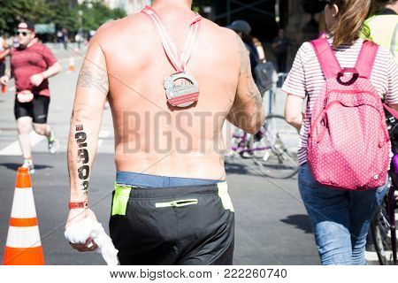 NEW YORK - JUL 16 2017: Athlete with medal around his neck walks on West 72nd St after finishing the Panasonic New York City Triathlon Race, the only International Distance triathlon in NYC.