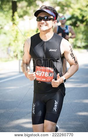 NEW YORK - JUL 16 2017: Athlete giving the thumbs up runs in Central Park during the 10k portion of the Panasonic New York City Triathlon Race, the only International Distance triathlon in NYC.