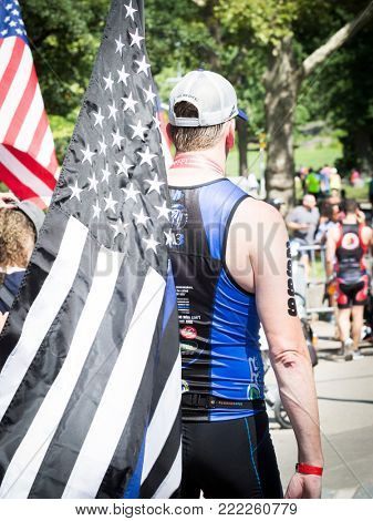 NEW YORK - JUL 16 2017: An athlete carrying the Thin Blue Line American Flag after finishing the Panasonic New York City Triathlon Race, the only International Distance triathlon in NYC.