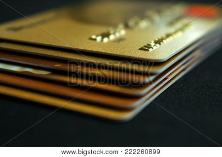 Stack of gold credit cards on dark background, close up view with selective focus. Different VIP credit cards, background with copy space. Paying, Buying.