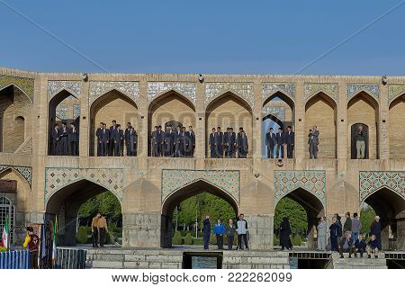 Isfahan, Iran - April 24, 2017: A children's choir of boys of school age lined up in the arched niches of the Khaju bridge to participate in a festive city event.