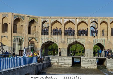 Isfahan, Iran - April 24, 2017: The boys in school uniform lined up in the niches of the Khaju bridge to participate in the city festival as a children's choir outdoors.