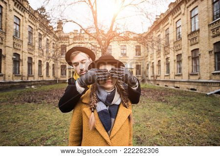man in gloves closing eyes of woman infront of building