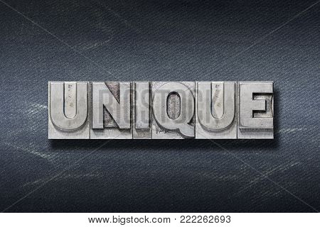 unique word made from metallic letterpress on dark jeans background