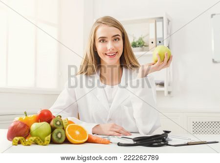 Smiling nutritionist woman with apple sitting at office, copy space. Healthy eating, right nutrition and slimming concept