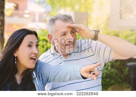 Nice mature couple sitting on green grass in summer park. Woman pointing with finger Couple looking and pointing something into distance. Outdoors