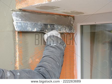 Contractor plastering wall  with putty knife, fiberglass mesh, plaster mesh after rigid insulation. House wall problem area insulation with stucco wall.