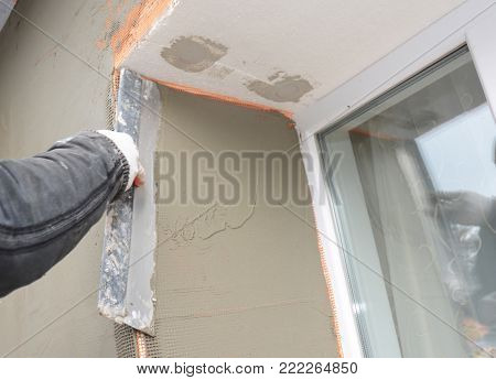 Builder plastering wall with spatula, fiberglass mesh, plaster mesh after foam rigid insulation. Window sill area insulation with stucco wall.
