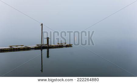 Single empty jetty, or boating dock, on glassy-still water