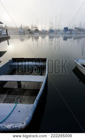 An image showing a single rowing boat on glassy-still waters