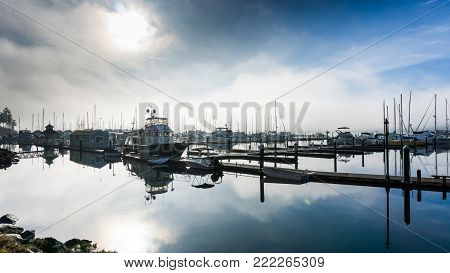 Misty morning image of a glassy still water harbor and boat dock