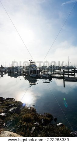 Sunrise and misty morning image of a harbor and boating dock