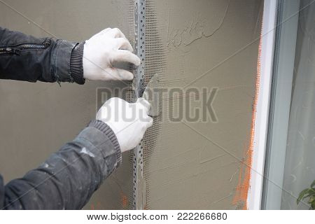 Contractor plastering wall  with putty knife, fiberglass mesh, plaster mesh after rigid insulation. Window sill area insulation with stucco wall.