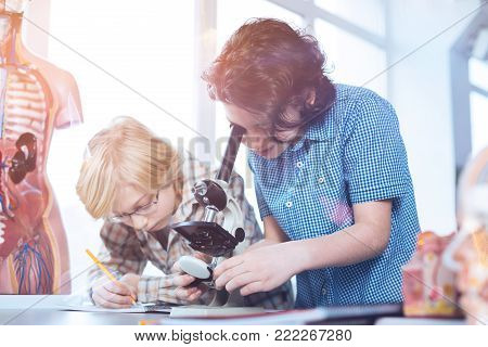 Closer look. Young persistent active boys working on their experimental assignment while one of them using a microscope and the other writing down data