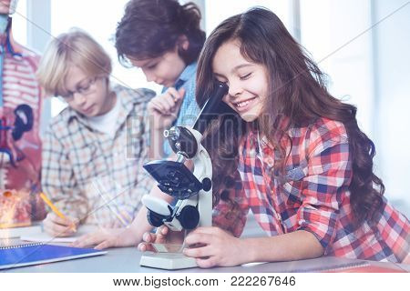 Tiny worlds. Eager sincere ambitious students attending biology class and using microscope for looking at the bacteria