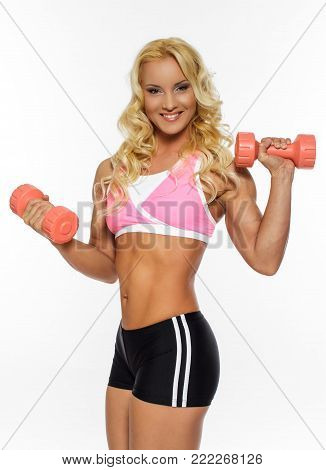 Awesome blond fitness woman in sportswear doing exercises with dumbells. Isolated on white background.
