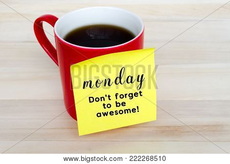Paper note stick on red coffee mug with text - Monday, Don't forget to be awesome!