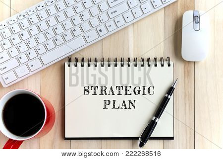 Top view of office desk and notepad with word - Strategic plan. Business concept.