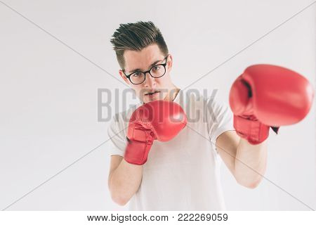 Cowardly funny young man in red boxing gloves. Nerd is wearing glasses