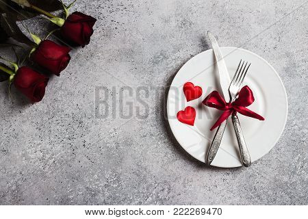 Valentines day table setting romantic dinner marry me wedding engagement with red rose gift and plate fork knife on grey background with copyspace. Love flower gift woman making proposal