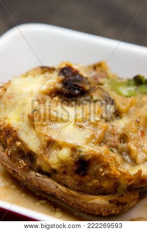 Large stuffed portobello mushrooms A large stuffed with vegetables and melted cheese Portobello mushrooms on a wooden board