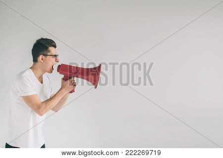 portrait of young man shouting using megaphone over green background Nerd is wearing glasses.