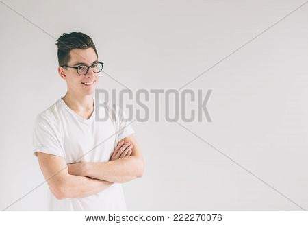 Portrait of young Nerd man wearing glasses and t-shirt standing with crossed arms and smiling isolated on white background.