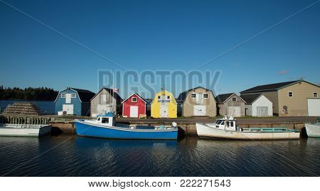 Blue fishing boat in front of oysters barns in New London, Prince Edward island also called PEI