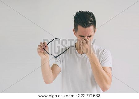 He is rubbing his nose and eyes because of weariness. Close up portrait of a funny man with eyeglasses. Weird young guy has eyesight problems.