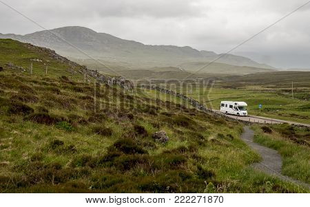 A view over the Highlands of Scotland with a motorhome parked up in a layby along the North Coast 500 route.