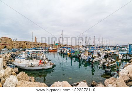 View on marina with yachts and ancient walls of harbor in Acre, Israel