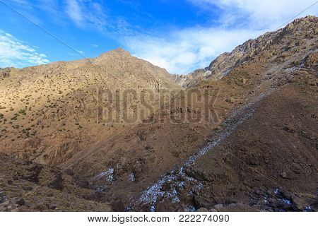 Atlas Mountains. Mountain slope with snow on walking hiking trail. Morocco, winter. Wild nature landscape.