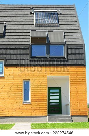 Modern house with energy saving and energy efficiency. Eco-house  with attic skylights, insulation, solar panels and solar water heater (SWH) system. Passive House Concept.