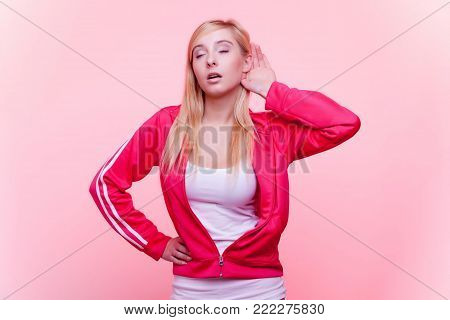 Sport fit  fitness woman with hand to ear listening pink background. Gossip