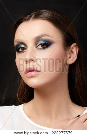 Closeup view of brown female eyes with evening makeup. Colorful pink and blue smokey eyes. Studio shot