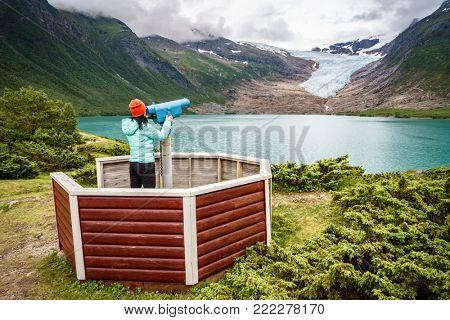 Girl tourist looks at a glacier on the viewing platform. Svartisen Glacier in Norway.