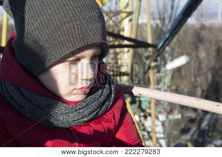 sad boy in scarf and hat, red jacket outdoor. winter. hurt boy in the park.