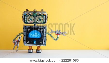 Hand wrench robot serviceman worker on yellow background. Cyborg toy lamp bulb eyes head, electric wires, capacitors vintage resistors.