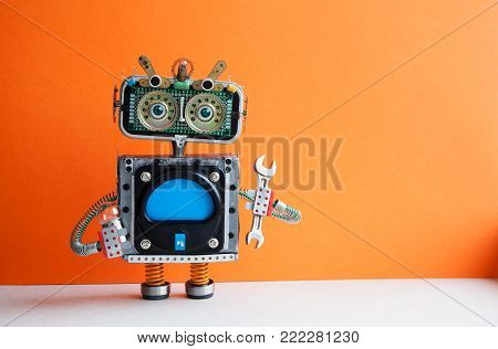 Robot handyman with hand wrench light bulb. Fixing maintenance concept. Creative design mechanic toy character. Orange wall, light floor background. Copy space