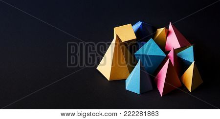 Colorful minimalistic composition abstract geometric solid figures on black textured paper background. Pyramid prism rectangular cube yellow blue pink green colored figures. shallow depth of field, copy space.