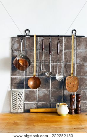 Retro kitchen still life interior. Brass utensils, chef accessories. Hanging copper kitchenware set. Spoon, skimmer, grater. Brown tiles ceramic wall. spoon, pitcher, spices. White background copy space