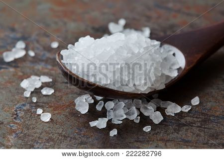 Sea salt condiment macro view. Natural mineral flavoring food preservative, Saline sodium chloride white crystal in wooden spoon, aged background. Shallow depth field